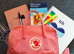 Lehrbuch, Kalender, Tablet, Stifte und ein Block finden sich im Rucksack vieler Studenten.